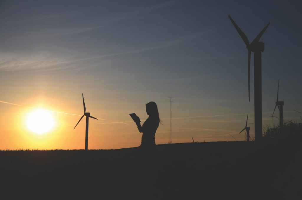 silhouette of woman holding book near windmills