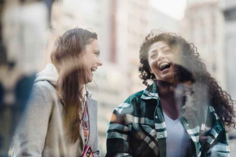 through glass of laughing diverse women