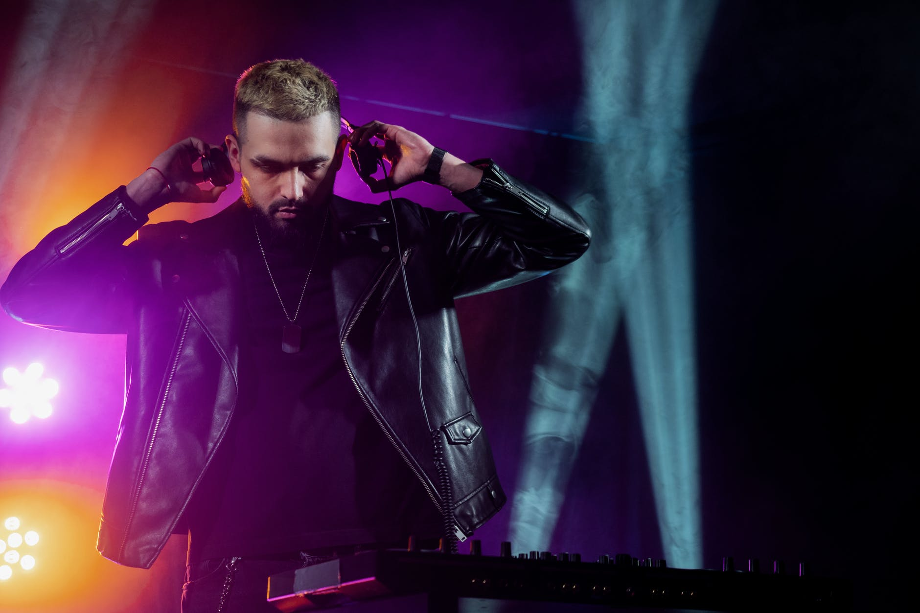trendy young male dj performing live concert in nightclub