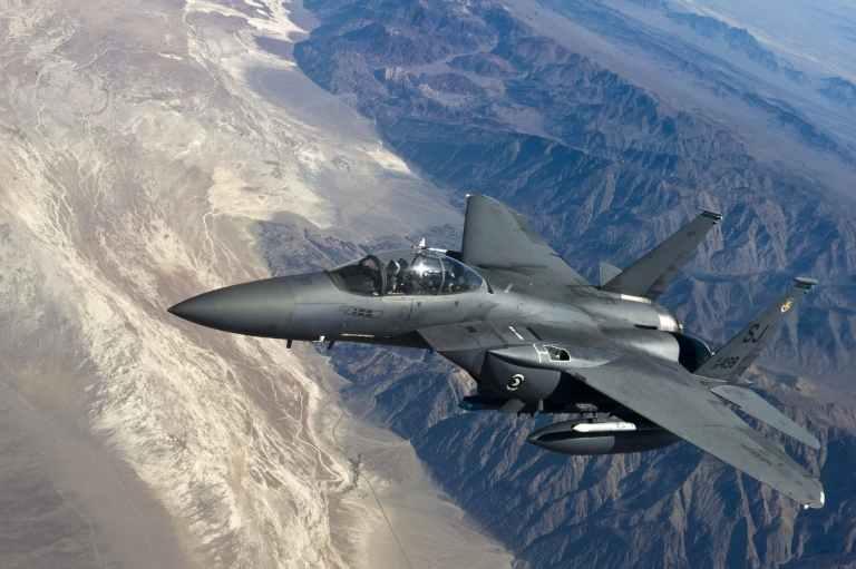 grey jet plane flying on top of white mountain