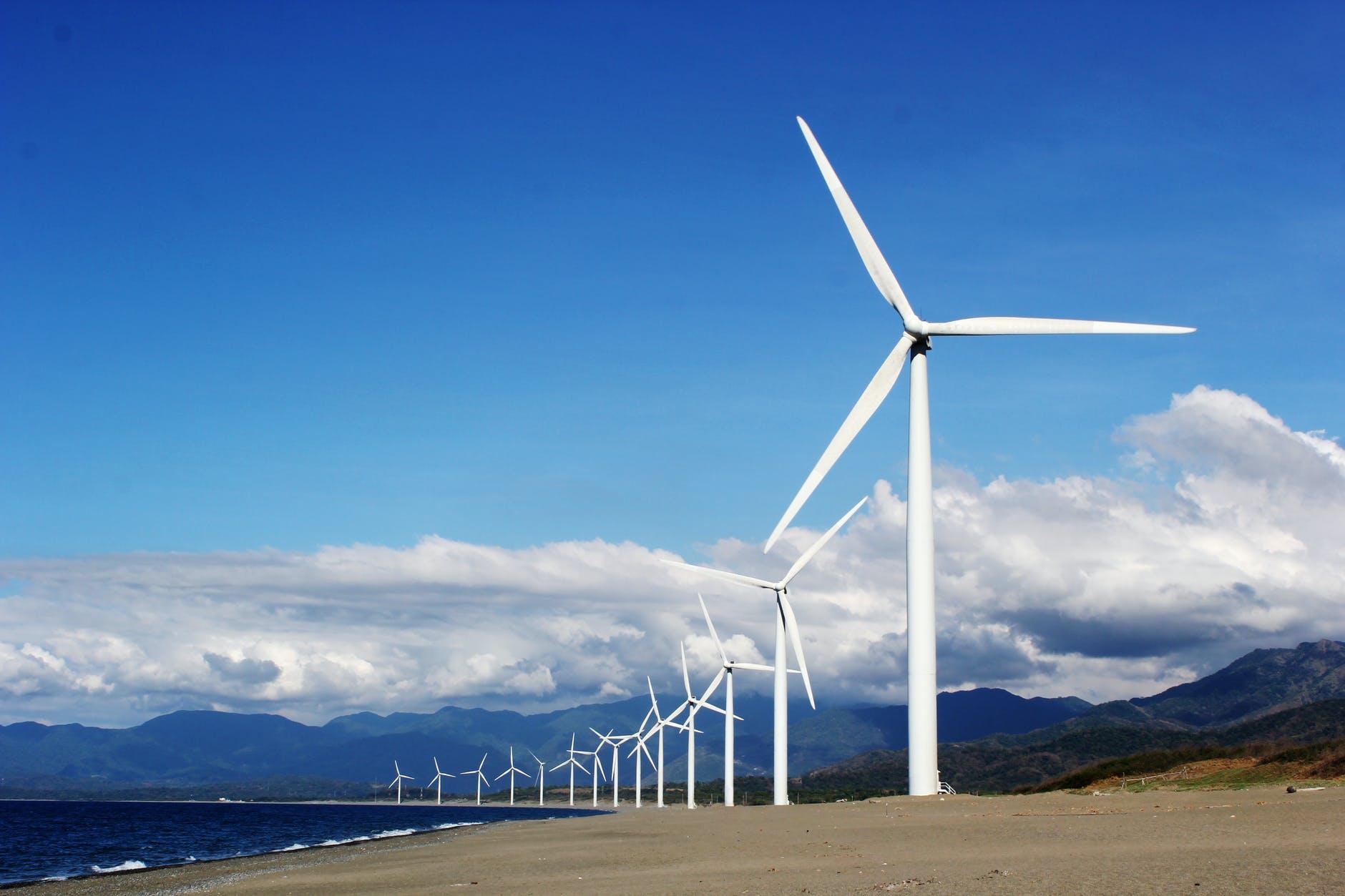 white wind turbines on gray sand near body of water