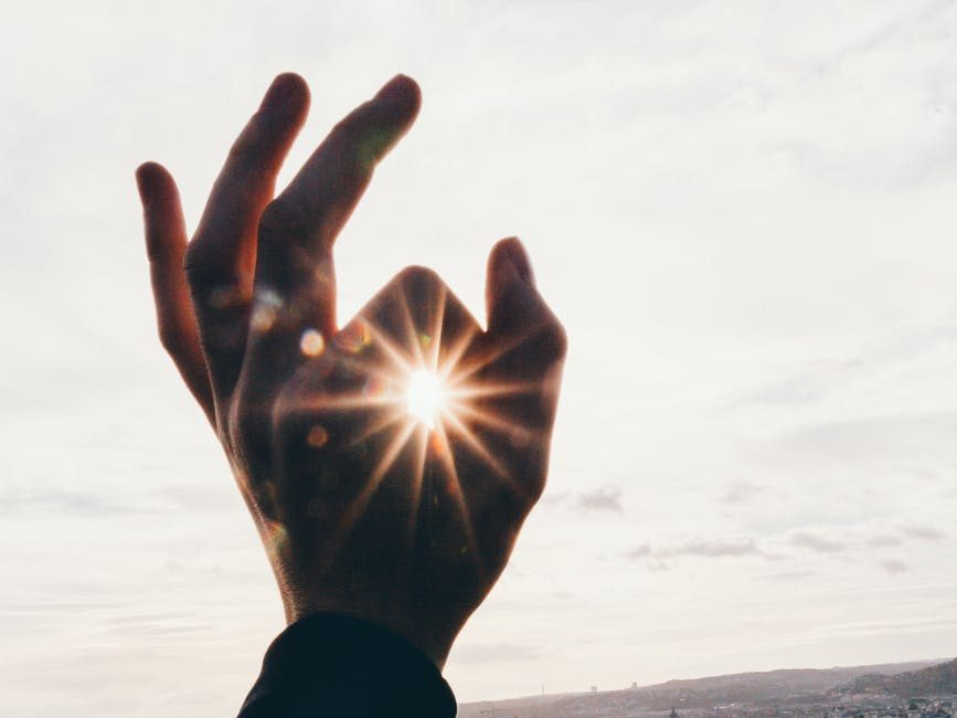 force perspective photography of hand and sun