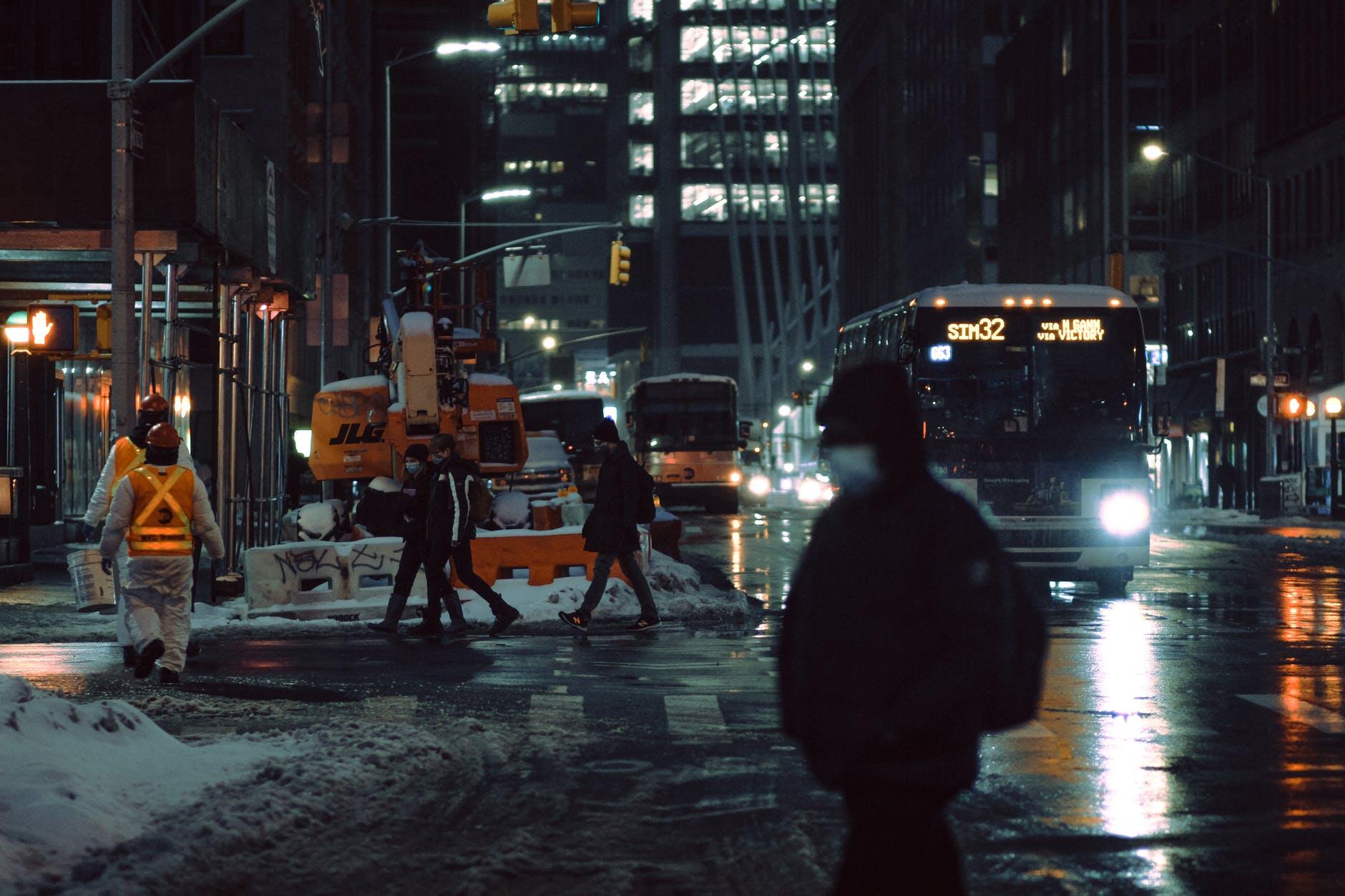 people walking on snowy road with bus on dark street