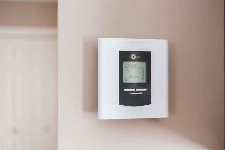 white thermostat hanging on the wall