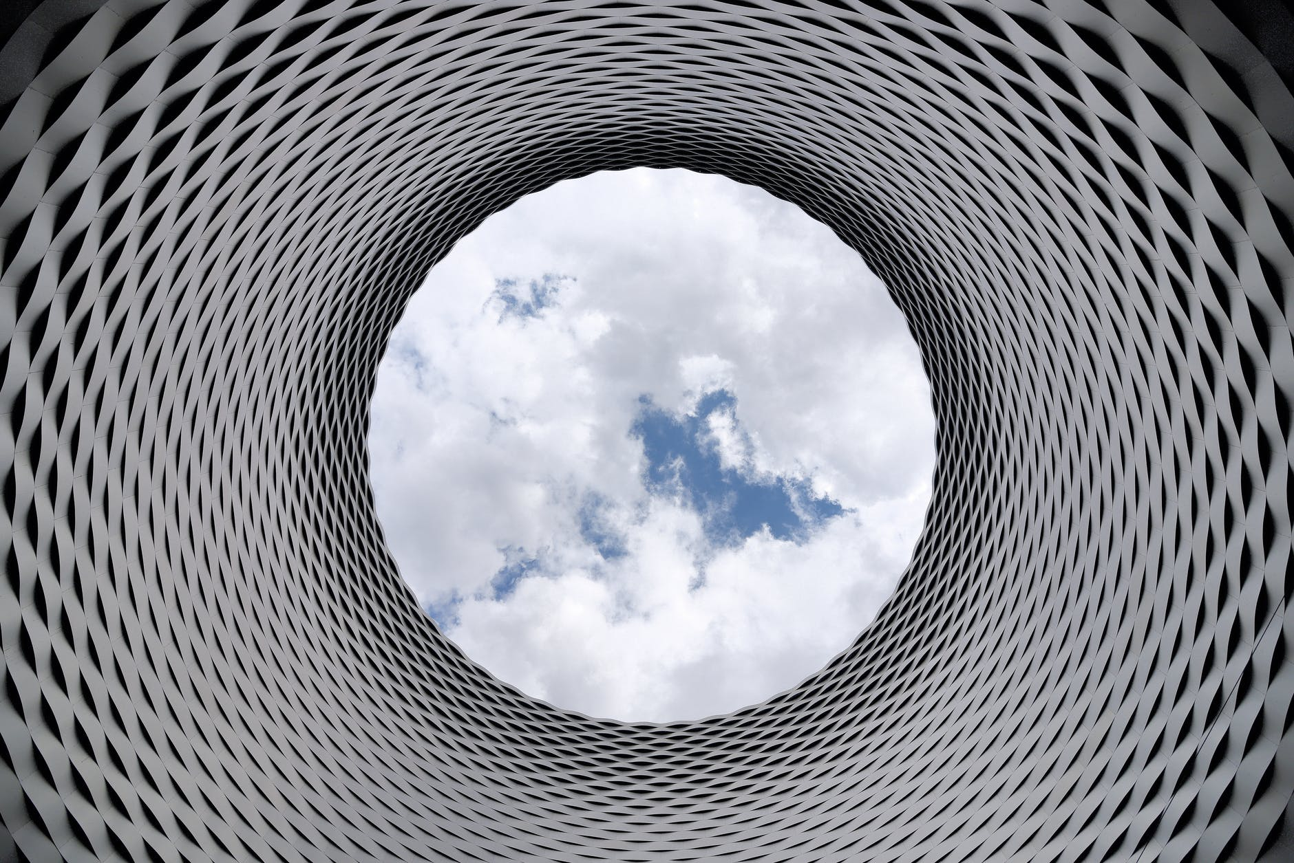 low angle photography of grey and black tunnel overlooking white cloudy and blue sky