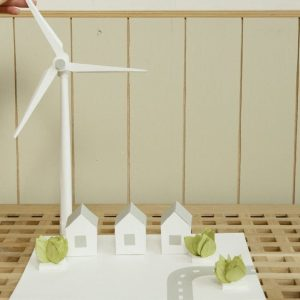 a scale model of houses and wind turbine on cardboard